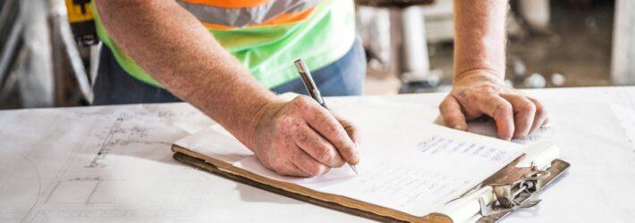 Ein Bauarbeiter füllt ein Formular aus, was auf einem Tisch liegt, auf dem verschiedene Pläne ausgebreitet sind.