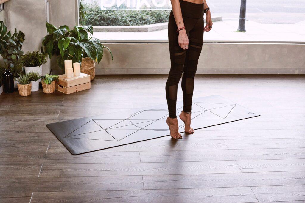 Eine Person mach Sport in einem Wohnraum. Sie steht barfuß auf einem Holzfußboden, hinter ihr liegt eine Yogamatte.