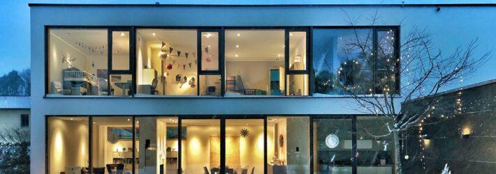 Ein modernes Wohnhaus in der Dämmerung mit Flachdach ist zu sehen. Der Garten ist verschneit, im Inneren sind die Lichter an.