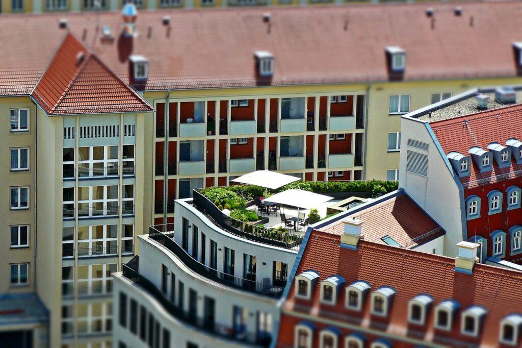 Mehrere Wohnhäuser sind zu sehen, davon eines mit einem Flachdach, auf dem eine Dachterrasse gebaut wurde.