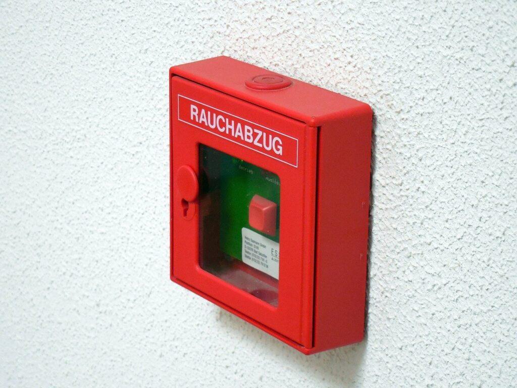 An einer weißen Wand hängt ein roter Rauch- bzw. Brandmelder.