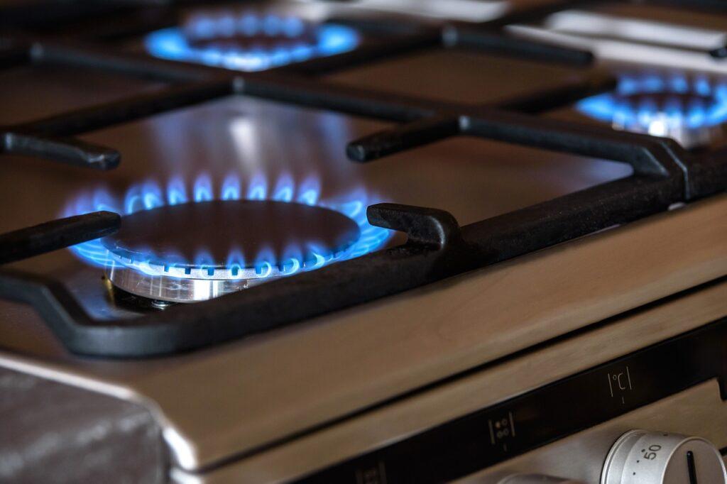 Ein Gasherd aus Edelstahl ist zu sehen, mehrere Flammen brennen.