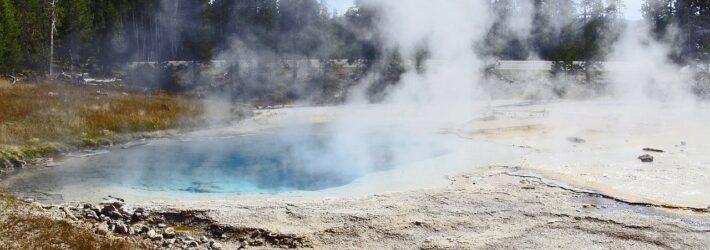 Eine Szenerie aus dem Yellowstone Nationalpark ist zu sehen, bei dem die Erdwärme beeindruckend als Nebel über einer Wasseroberfläche sichtbar wird.