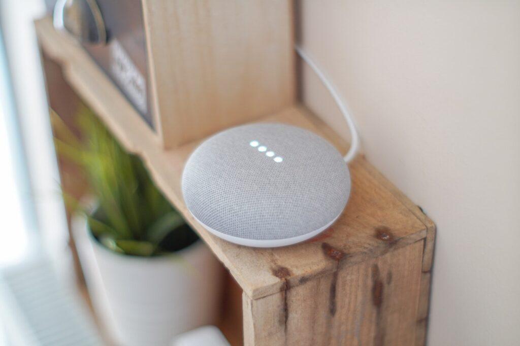 Ein grauer, runder Speaker steht auf einem Holzkisten-Regal.