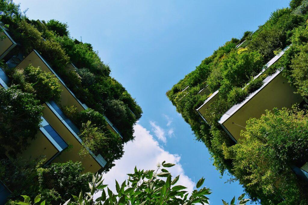 Von unten aufgenommen blickt man an zwei Hochhäusern empor in den blauen Himmel. Beide Häuser sind über und über mit grünen Pflanzen bewachsen.