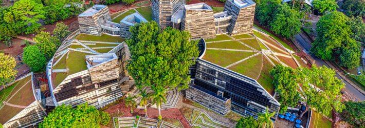 Man sieht aus der Luft aufgenommen einen modernen Gebäudekomplex mit Dachbegrünung