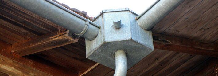 Ein Dach von schräg unten aufgenommen, an dem sich zwei Regenrinnen zur Dachentwässerung in einer Ecke treffen und in in ein Fallrohr abwärts münden.