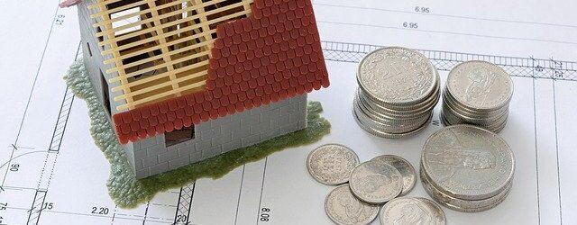 Auf einigen Papieren und Plänen steht ein kleines Haus-Modell mit halb fertigem Dach, daneben liegen einige Münzen.