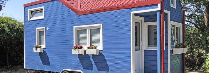 Ein Tiny House auf Rädern ist zu sehen. Es hat eine blaue Holzverkleidung und ein rotes Dach.
