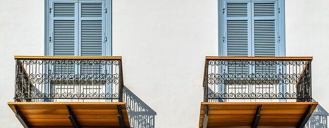 Zwei Balkons aus Holz sind nebeneinander an einer weißen Hausfassade angebracht.