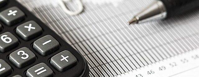 Auf einem Blatt Papier liegt ein Taschenrechner und ein Stift.