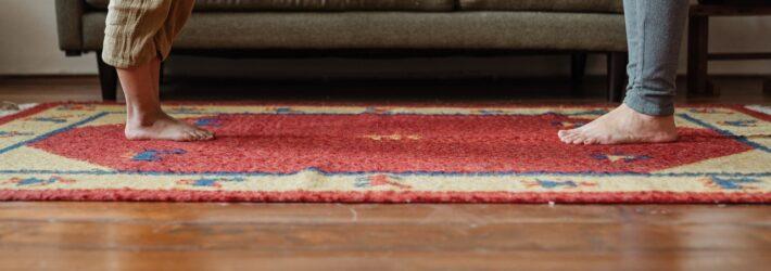 Zwei Menschen stehen sich gegenüber. Ihre nackten Füße stehen auf einem Teppich, der über Parkett gelegt wurde.