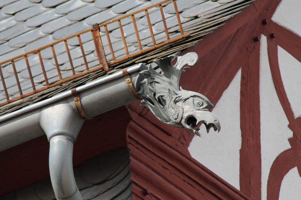 Ein Fachwerkhaus mit rotbraunen Holzbalken wird von einer Metall-Darinne mit Drachenausfluss geziert
