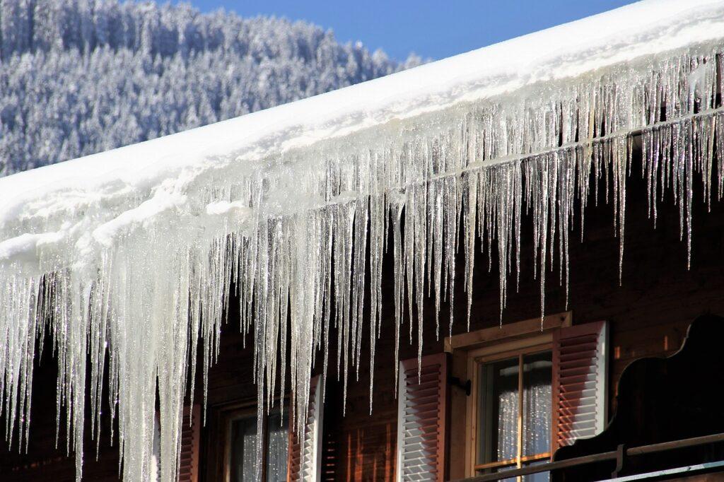 An einem Hausdach hängen zahllose große Eiszapfen.