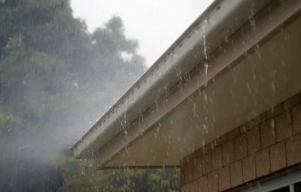 Es regnet in Strömen. An einem Hausdach ist eine Regenrinne aus Kunststoffe befestigt.