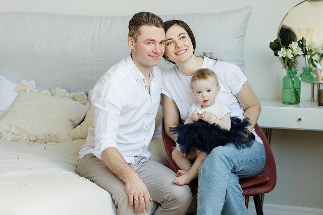 In einem modern eingerichteten Schlafzimmer sitzen ein junger Mann, eine junge Frau mit einem Baby auf dem Schoß zusammen auf dem Bett.