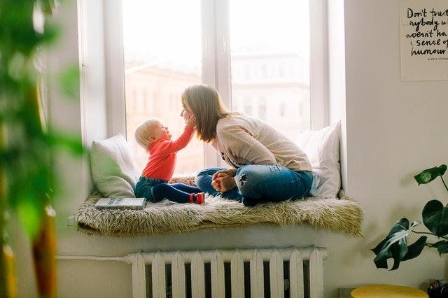 Auf einer Fensterbank sitzt eine junge Frau mit einem Kleinkind, das ihr die Wange streichelt.