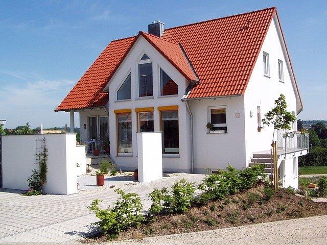 Ein neu gebautes Einfamilienhaus mit weißen Außenwänden und einem roten Dach steht auf einem Grundstück.