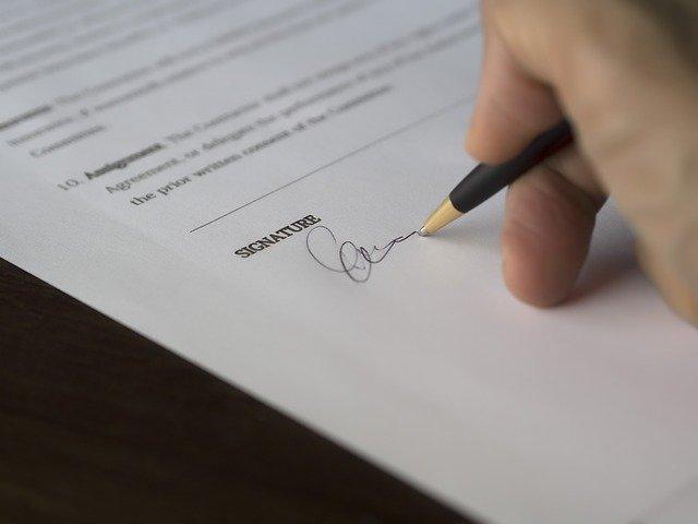 Ein Antrag wird handschriftlich unterschrieben.