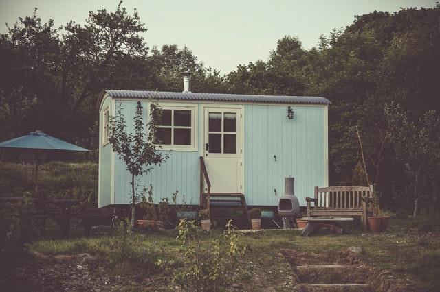 Ein Tiny House in Hellblau steht in einem grünen Garten.