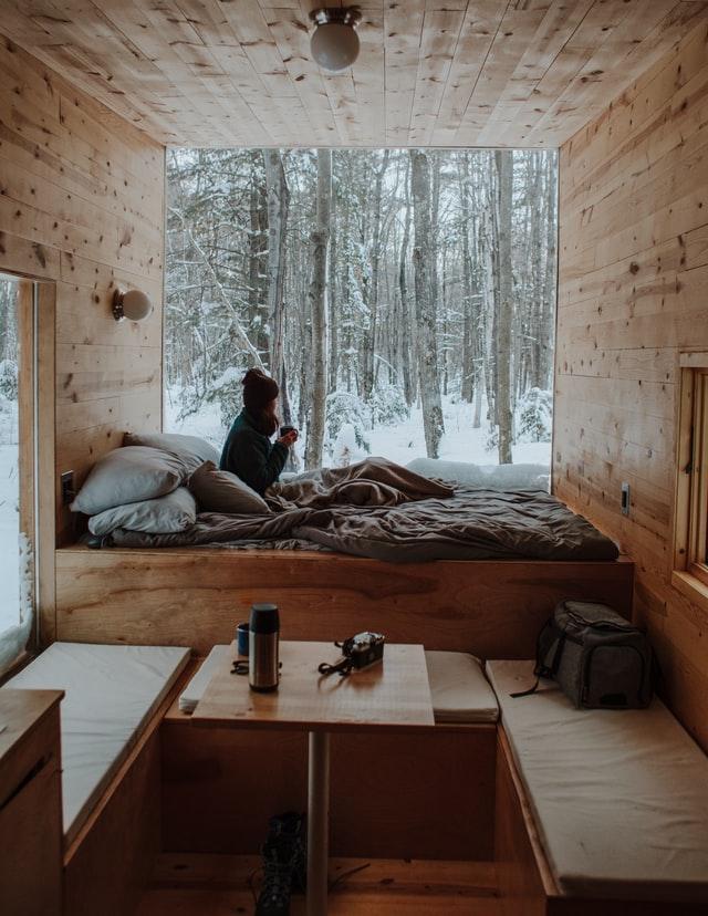 Ein minimalistisch eingerichtetes Innere eines Tiny House ist zu sehen: Es ist komplett mit Holz verkleidet und an der Fensterfront ist ein Bett, in dem eine Frau sitzt, die aus dem Fenster schaut.