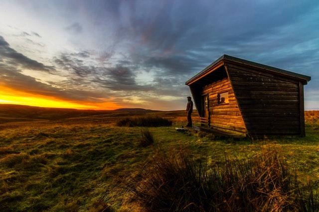 Ein Tiny House aus Holz steht mitten in einer einsamen Landschaft, davor steht eine Person und schaut in den Sonnenuntergang