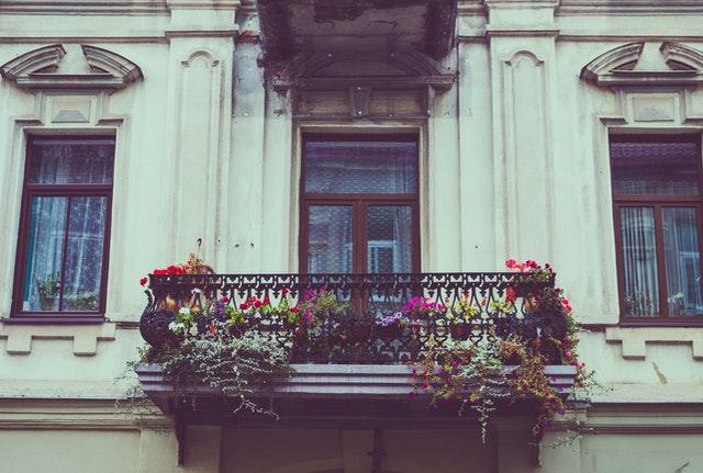 Eine Altbau-Fassade eines Hauses mit einem Balkon aus Eisen ist zu sehen