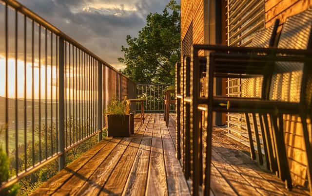 Auf einem Holzbalkon mit Metall-Geländer stehen zwei Stühle im Sonnenuntergang.