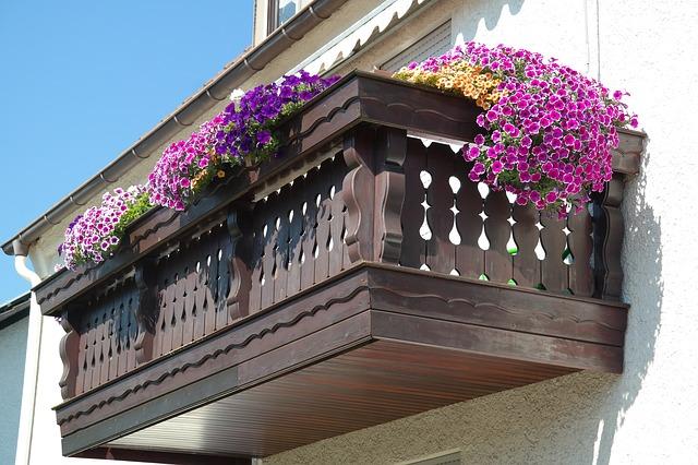 Ein freitragender Balkon aus Holz hängt an einer hellen Hauswand.