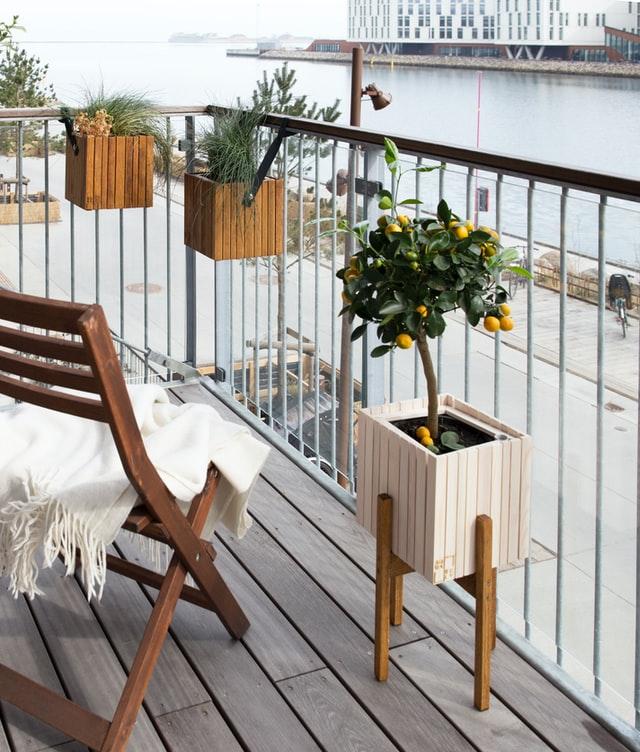 Ein Balkon mit Blick auf einen Fluss. Er ist mit verschiedenen Pflanzkübeln aus Holz und einem Stuhl bestückt.