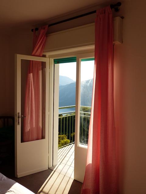 Eine geöffnete Balkontür führt auf einen Balkon hinaus.