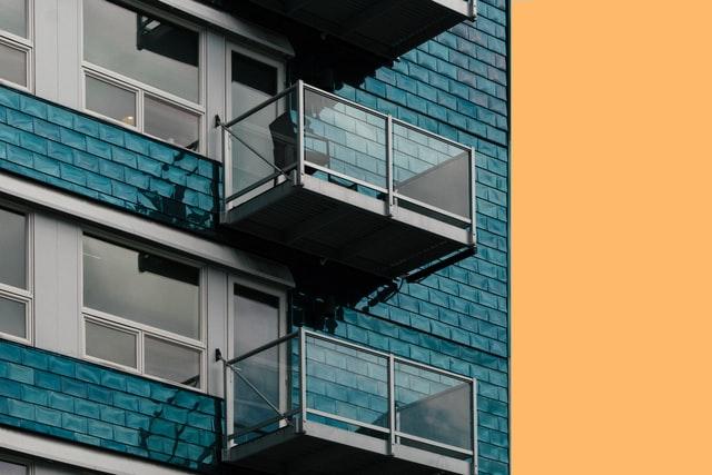 An einer blauen Hausfassade sind freitragende Balkone aus Metall und Glas angebracht.