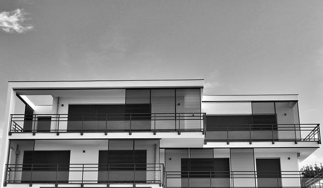 Eine schwarz-weiß-Aufnahme eines modernen Hauses mit großen Fenstern und Flachdach.