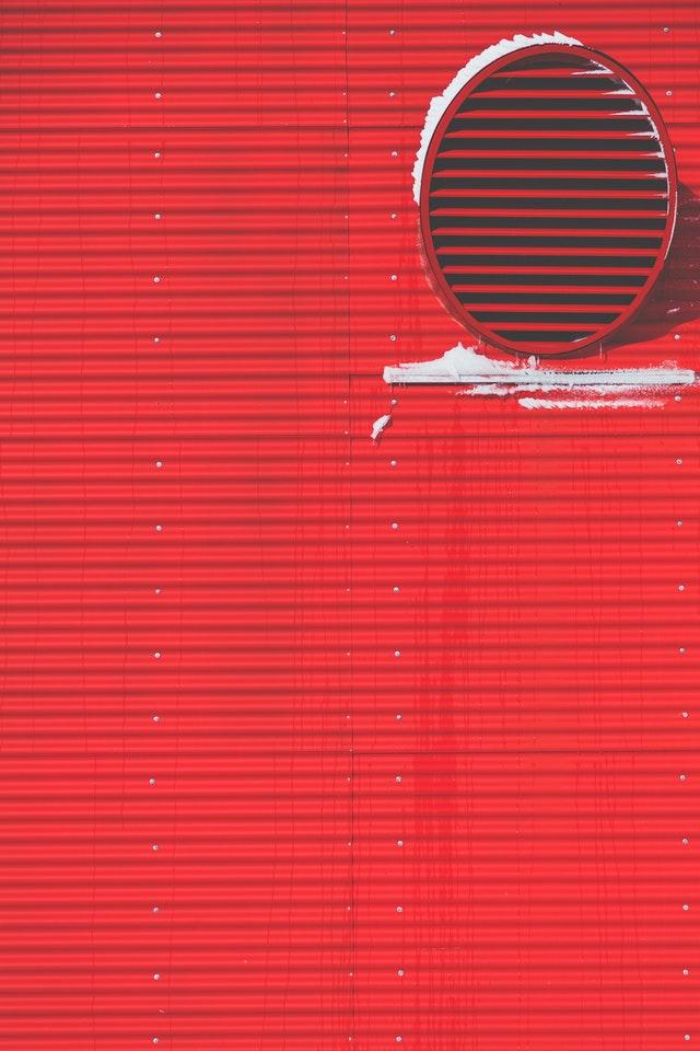 An einer roten Außenwand ist ein großer Abluftauslass zu sehen.