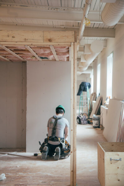 Ein Mann kniet auf einem Boden aus Holzfasern. Um ihn herum wird ein neues Haus gebaut