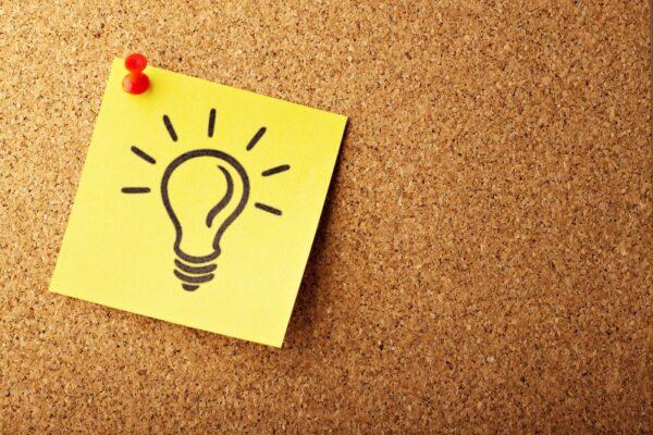Auf einem Stück Kork ist ein Post-It mit einer Glühbirne aufgezeichnet, angepinnt