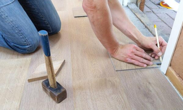 Jemand hpockt auf dem Boden und verlegt Laminatplatten. Dazu arbeitet er mit einem Bleistift und einem Hammer
